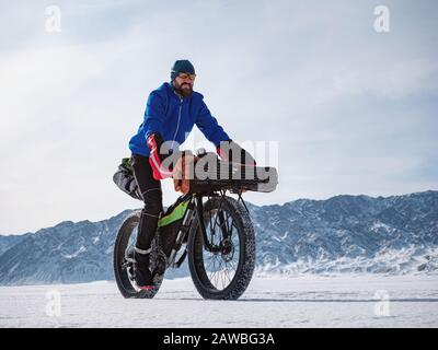 A male traveler rides a fatbike on a frozen mountain lake. Traveling in the winter. Extreme expedition. - Stock Photo