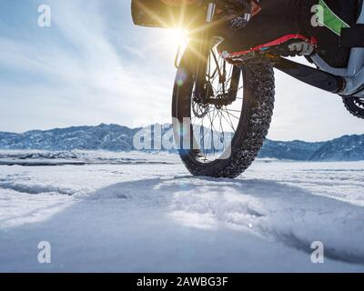Close-up of a fatbike wheel, rolling on a frozen mountain lake. Traveling in the winter. Extreme expedition. - Stock Photo