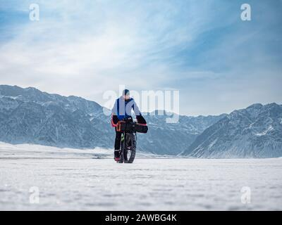 Traveler rides a fat bike on the ice of a frozen mountain lake. Traveling in the winter. Extreme expedition. - Stock Photo