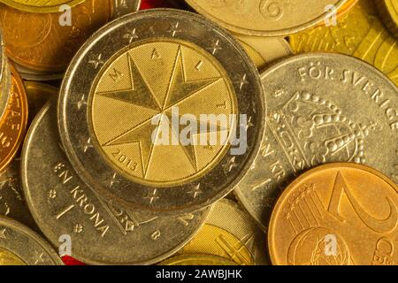 Coins of different countries. a lot of metal coins of different denominations and various countries. financial background. euro coin in the foreground - Stock Photo