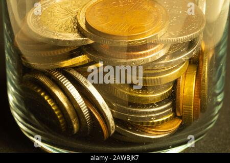Coins of the different countries in a glass jar. a lot of metal coins of different denominations and various countries. finance background - Stock Photo
