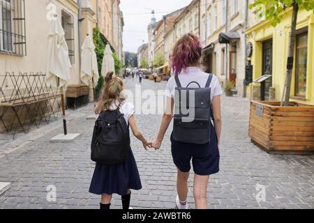 Children going to school, two girls sisters holding hands, back view - Stock Photo
