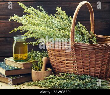 Absinth blooming herb in a wicker on wooden rustic background with bunch of sagebrush flowers, mortar and blossoms all around on old books, closeup, c