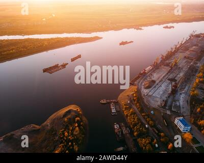 Port river cranes loading ships on barges delivery, sunset. Aerial drone - Stock Photo