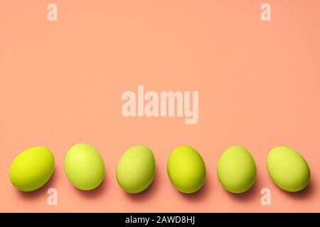 row of yellow eggs on pink background with copyspace. easter advertise design - Stock Photo