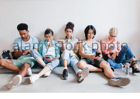 Unpleased girl with bronze skin sitting on the floor beside university friends which don't pay attention to her. Indoor portrait of busy students waiting for test's result. - Stock Photo