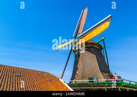 Zaanse schans, Netherlands - April 1, 2016: People visiting old windmill in dutch traditional village in North Holland - Stock Photo