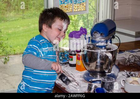 A cute little boy covered in flour makes cookies in grandma's kitchen - Stock Photo