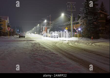 Snowy street in downtown Canmore, Alberta, Canada at night - Stock Photo