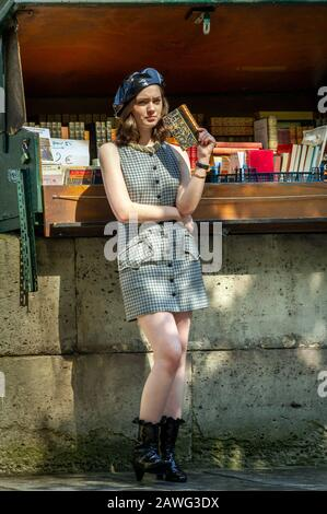 Young woman with a book at antique book store on Seine embankment in Paris - Stock Photo