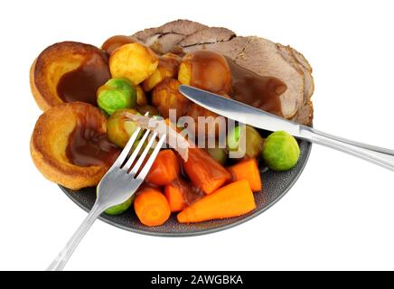 Traditional roast beef dinner with roasted potatoes and Yorkshire pudding and vegetables, isolated on a white background