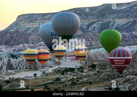 A colourful group of hot air balloons take off from a valley near Goreme in the Cappadocia region of Turkey at sunrise. - Stock Photo