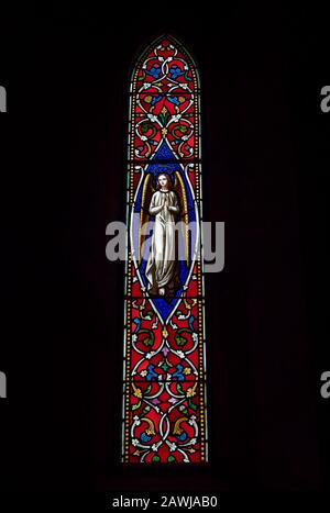 A Victorian Stained Glass Window depicting an Angel, within the Church of St Michael and All Angels next to Ford Castle in Northumberland. - Stock Photo