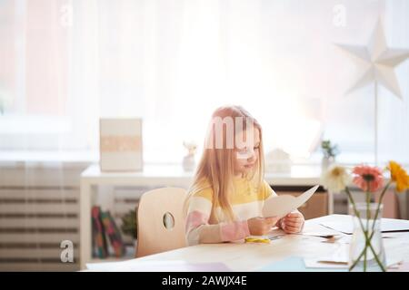 Warm toned portrait of cute girl making holiday card for Mothers day or Valentines day while sitting at table in cozy home interior, copy space Stock Photo