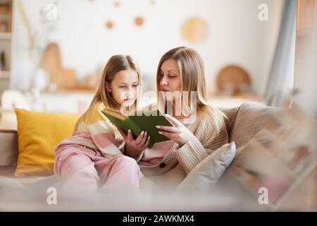 Warm-toned portrait of mature mother reading book to little girl while sitting on sofa in cozy home interior, copy space