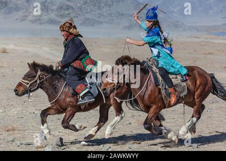 Ulgii, Mongolia, October Golden eagle festival traditional Kazakh games horse chasing couple Stock Photo