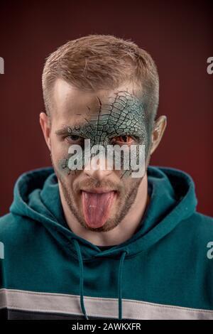 man with professional horror movie make-up green lizard on dark red background. lizard eye - Stock Photo