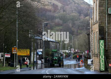 Marsden, UK. 9th February, 2020. Storm Ciara leaves a trail of damage in the Calder valley.  Rain has washed stones and  a railway sleeper onto the Rochdale to Todmorden Road.  A tree has fallen across the railway line.  A tractor is been used to take away flood water and empty it into the Rochdale canal.  Walsden, Calder Valley, West Yorkshire, UK. Credit: Barbara Cook/Alamy Live News - Stock Photo
