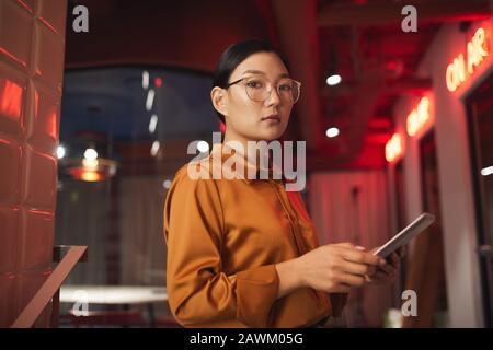 Waist up portrait of modern Asian businesswoman holding tablet and looking at camera while posing outdoors, copy space