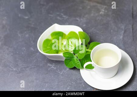 Cup of Silver Spurflower tea and leaves in a white bowl on stone slate plate.