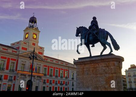 Clock Tower and Equestrian statue of King Charles III, monument on Puerta del Sol in Madrid, Spain at dusk - Stock Photo
