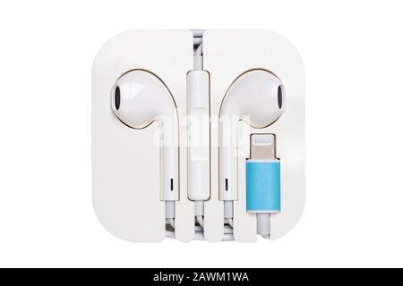 Earphones isolated. Close-up of white earphone to listen to music isolated on a white background. Wired headphone with noise cancelling. Macro photogr - Stock Photo