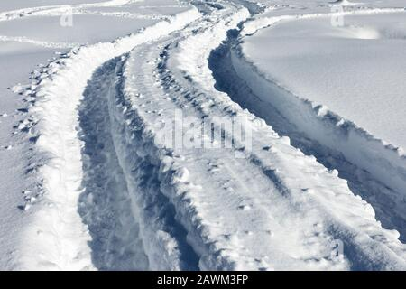 Traces of the car in the snow. Traces on snow. - Stock Photo