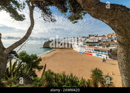 View of beach in Carvoeiro town with colorful houses on coast of Portugal. The village Carvoeiro in the Algarve Portugal. - Stock Photo