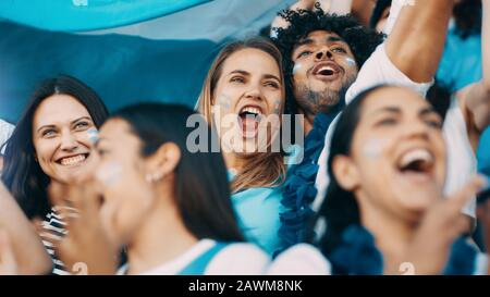 Excited sports fans at live game shouting and cheering for their team. People watching football match chanting to cheer argentinian national team.