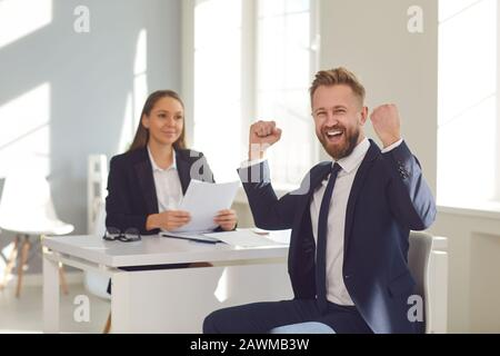 Successful interview. A man in a suit rejoices at a new job sitting at a table with a woman employer in a white office. - Stock Photo