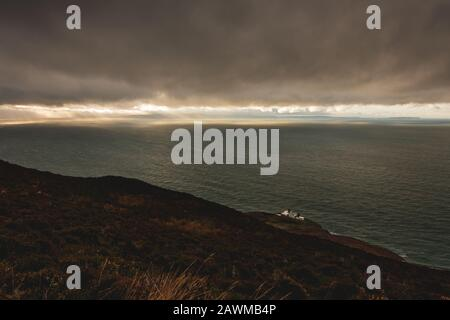 Views from the Mull of Kintyre to Northern Ireland and Rathlin island in dramatic weather conditions in winter, Scotland, UK