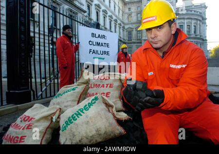 Greenpeace demonstrators leave a pile of coal outside Downing Street protesting against climate change in 2005. The Prime minister had promised to cut Britain's emission of climate damaging pollution. - Stock Photo