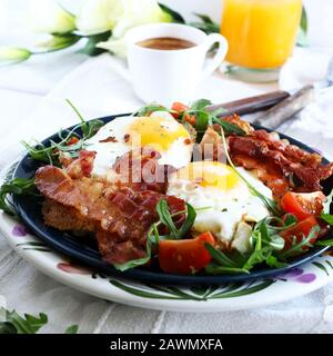 Breakfast with fried eggs, bacon, fresh salad, orange juice and coffee on table. Top view. White background - Stock Photo