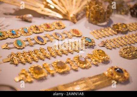 Luxury gold jewelry - shiny gold bracelets and handheld fans. variety of beautiful antique jewelry of royal family on display at shop. Expensive Gift - Stock Photo