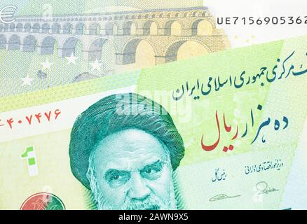 A close up image of a green Iranian ten thousand rial bank note with a blue and green five euro note from France in macro - Stock Photo
