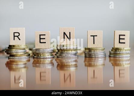 The letters of the word Rente put on coins on square surfaces - Stock Photo