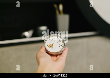 Hand holding eco solid shampoo in metal can in modern bathroom on background of stylish black shelf with plastic free natural organic essentials. Zero - Stock Photo