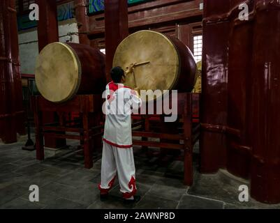 Drummer beating drum in interior of Drum Tower or Gulou, Beijing, China, Asia - Stock Photo