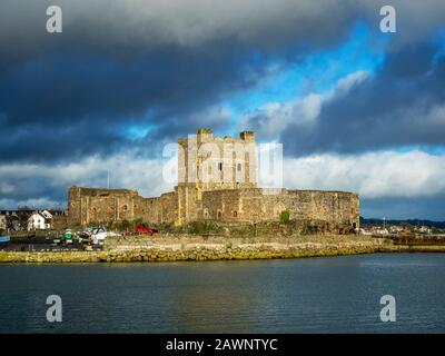 Medieval Norman Castle in Carrickfergus near Belfast, Northern Ireland, with marina in winter. Dramatic sky with dark stormy clouds. Sunset light