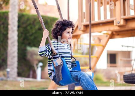 A smiling kid boy on a swing outdoor. Childhood and activity concept