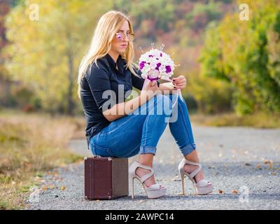 Teen girl sitting on boxy baggage case countryroad denim pants legs heels hand holding flowery bouquet indifferent - Stock Photo
