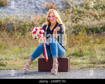 Teen girl sitting on boxy baggage case denim pants legs heels hand holding flowery bouquet looking at camera slight smile - Stock Photo
