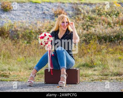 Teen girl sitting on boxy baggage case denim pants legs heels hand holding flowery bouquet smiling positive feeling expected expecting expect looking - Stock Photo