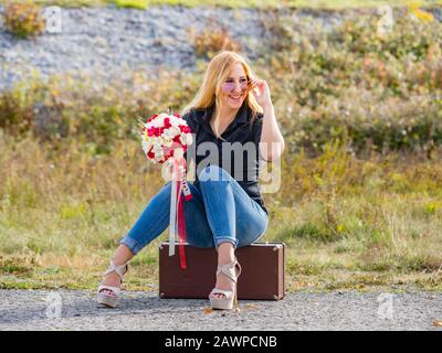 Teen girl sitting on boxy baggage case denim pants legs heels looking away aside smiling positive feeling expected expecting expect - Stock Photo