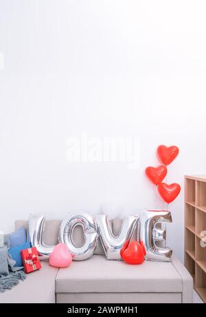 Foil love balloons and gifts on a sofa with white wall in background for Valentine's day, Mother's day surprise design concept. - Stock Photo