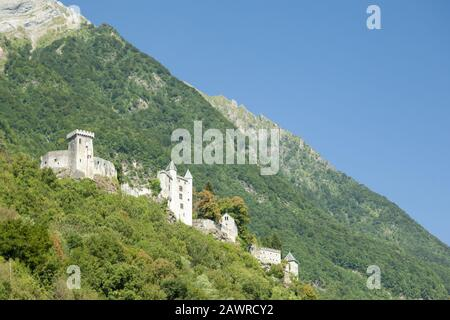 A beautiful low angle shot of the Fortress of Miolans on mountain hills surrounded by greenery - Stock Photo