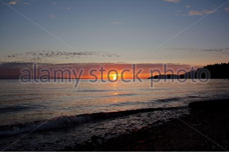 First light in the early morning with sun rising above Strait of Georgia viewed from Vancouver Island beach - Stock Photo