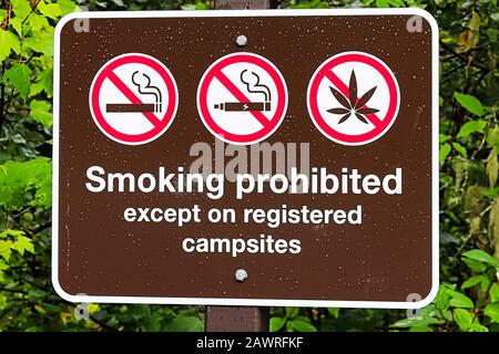 A smoking prohibited except on registered campsite sign - Stock Photo