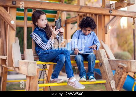 Two kids boy and girl playing games on tablet outdoor. Children and gadget addiction concept