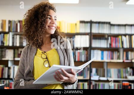 Education, high school, university, learning and people concept. Smiling student girl reading book - Stock Photo